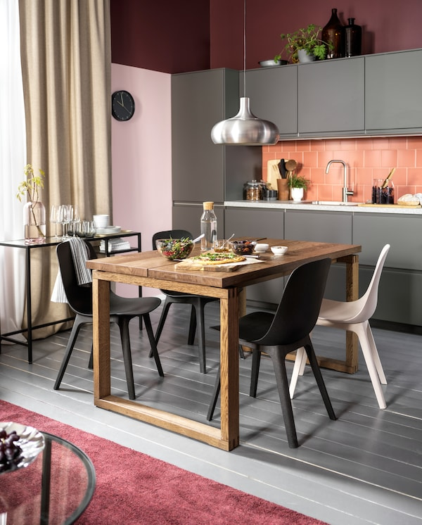A kitchen with dark grey fronts, a table in oak veneer, chairs in anthracite/white and an aluminium-coloured pendant lamp.