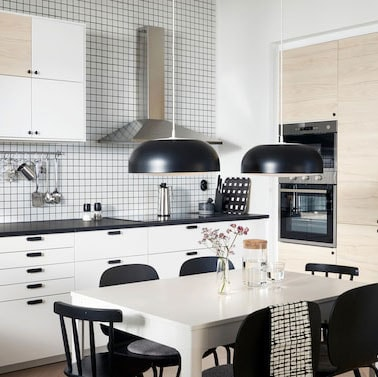 A kitchen with doors in white and light ash effect, two black pendant lamps, a white table and black chairs.