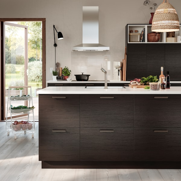 A kitchen with drawers and doors in dark brown ash effect, a pendant lamp shade made from seagrass and a white trolley.