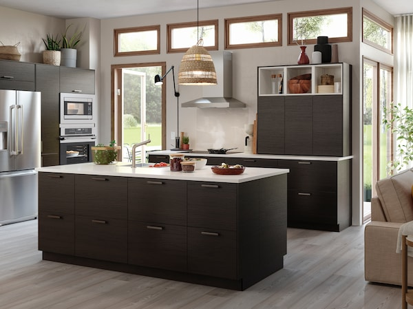 A kitchen with drawers and doors in dark brown ash effect and a kitchen island with a worktop in white/quartz.