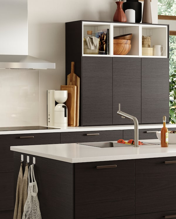 A kitchen with fronts in brown ash effect and a kitchen island with a kitchen mixer tap and an inset sink in stainless steel.