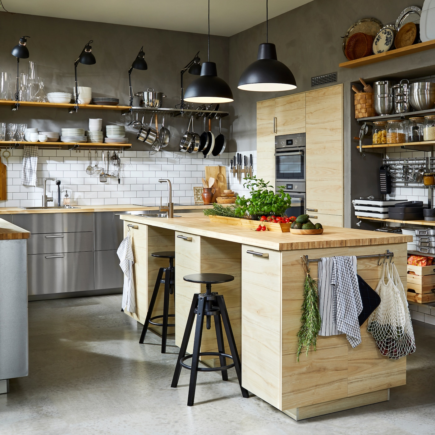 A kitchen with fronts in stainless steel, two black pendant lamps and a spacious kitchen island with two black bar stools.