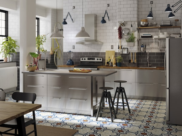 A kitchen with fronts in stainless steel, worktops in oak and grey, blue industrial work lamps and two black bar stools.