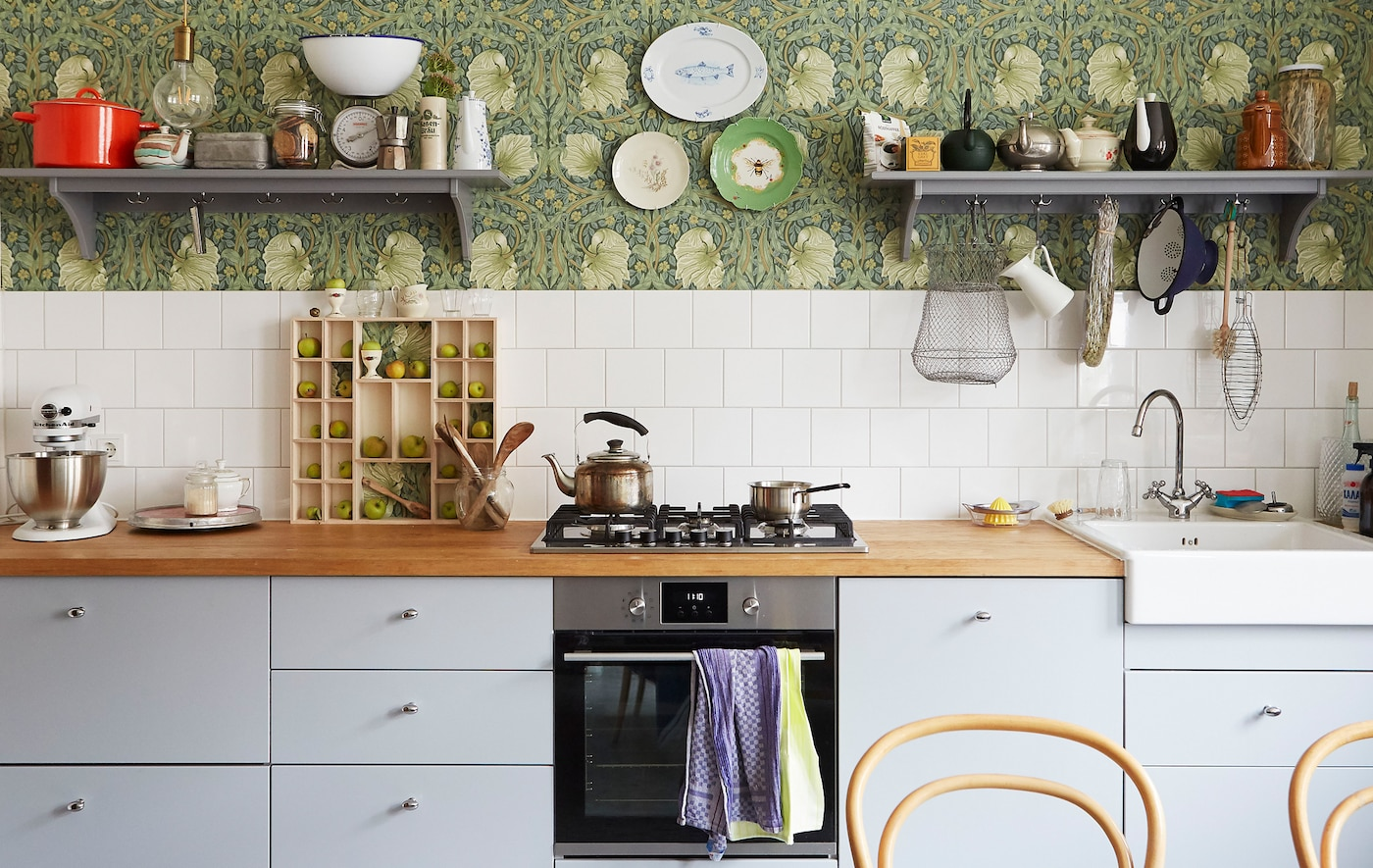 A kitchen with gray cabinets and built-in cooker, a wooden worktop and shelves on patterned floral wallpaper.
