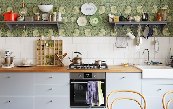 A kitchen with grey cabinets and built-in cooker, a wooden worktop and shelves on patterned floral wallpaper.