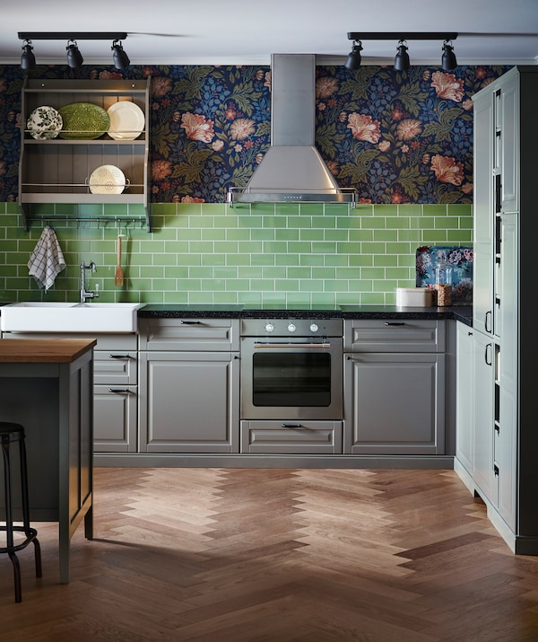 A kitchen with grey cabinets, green tiles and floral wallpaper, with a stainless steel extractor hood.