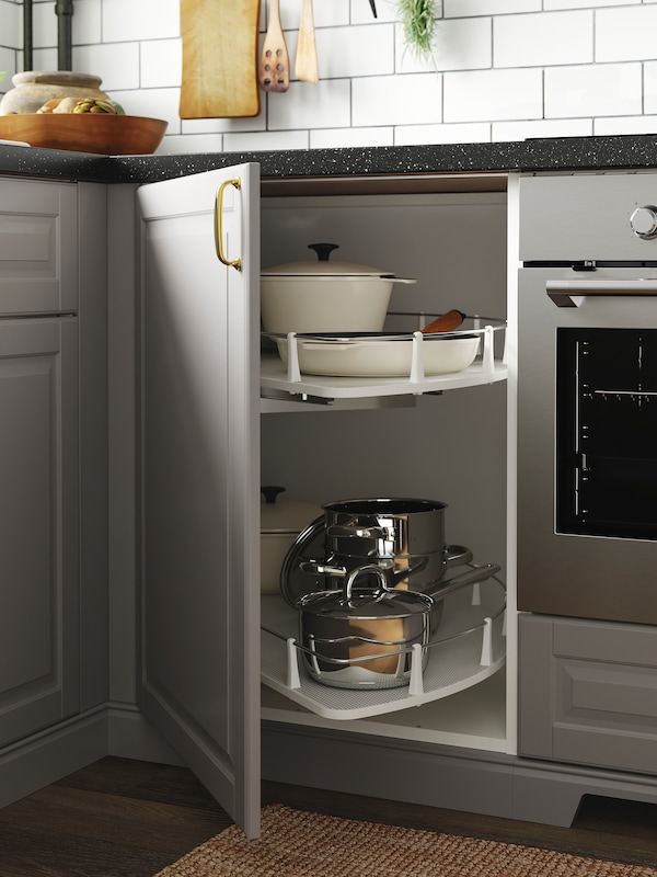 A kitchen with grey doors and an open corner cabinet where a carousel stores pots, pans and dishes.