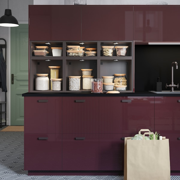 A kitchen with high-gloss drawers and doors in dark brown-red and TUTEMO open cabinets in anthracite with food in glass jars.