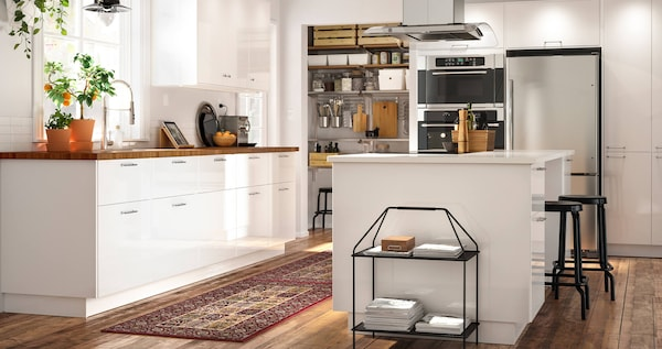 A kitchen with high-gloss white doors and a wooden countertop with a kitchen island with a white countertop.