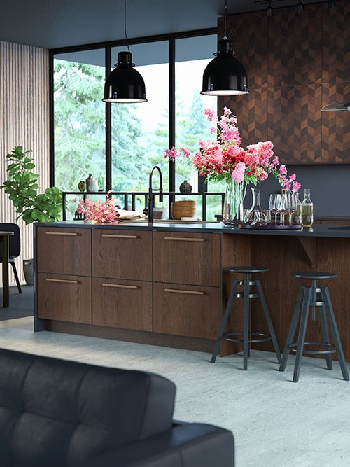 A kitchen with industrial décor including a kitchen island in dark wood, two black bar stools, two black pendant lamps, a vase with pink and red flowers.