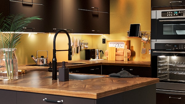 A kitchen with kitchen doors in anthracite, a walnut veneer countertop and an oven and microwave oven in black.