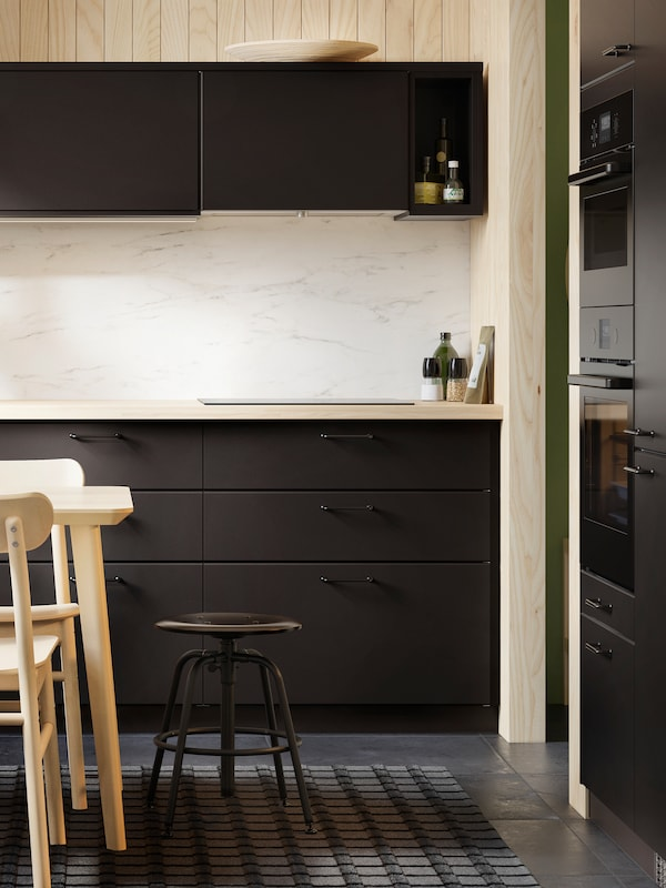 A kitchen with KUNGSBACKA anthracite cabinet doors and drawer fronts, a marble effect splashback and a black stool.