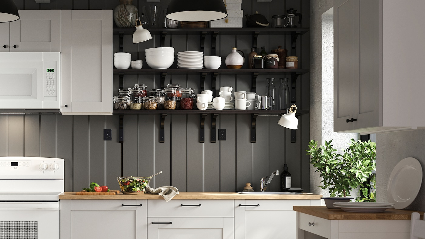 A kitchen with light gray cabinets, a white oven and microwave and black wall-mounted shelves storing tableware.