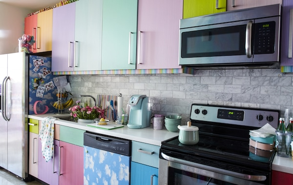 A kitchen with multicoloured doors and a white worktop.
