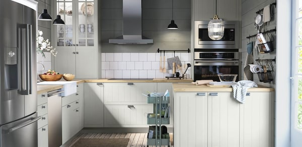 A kitchen with off white cabinets and stainless steel hardware and appliances