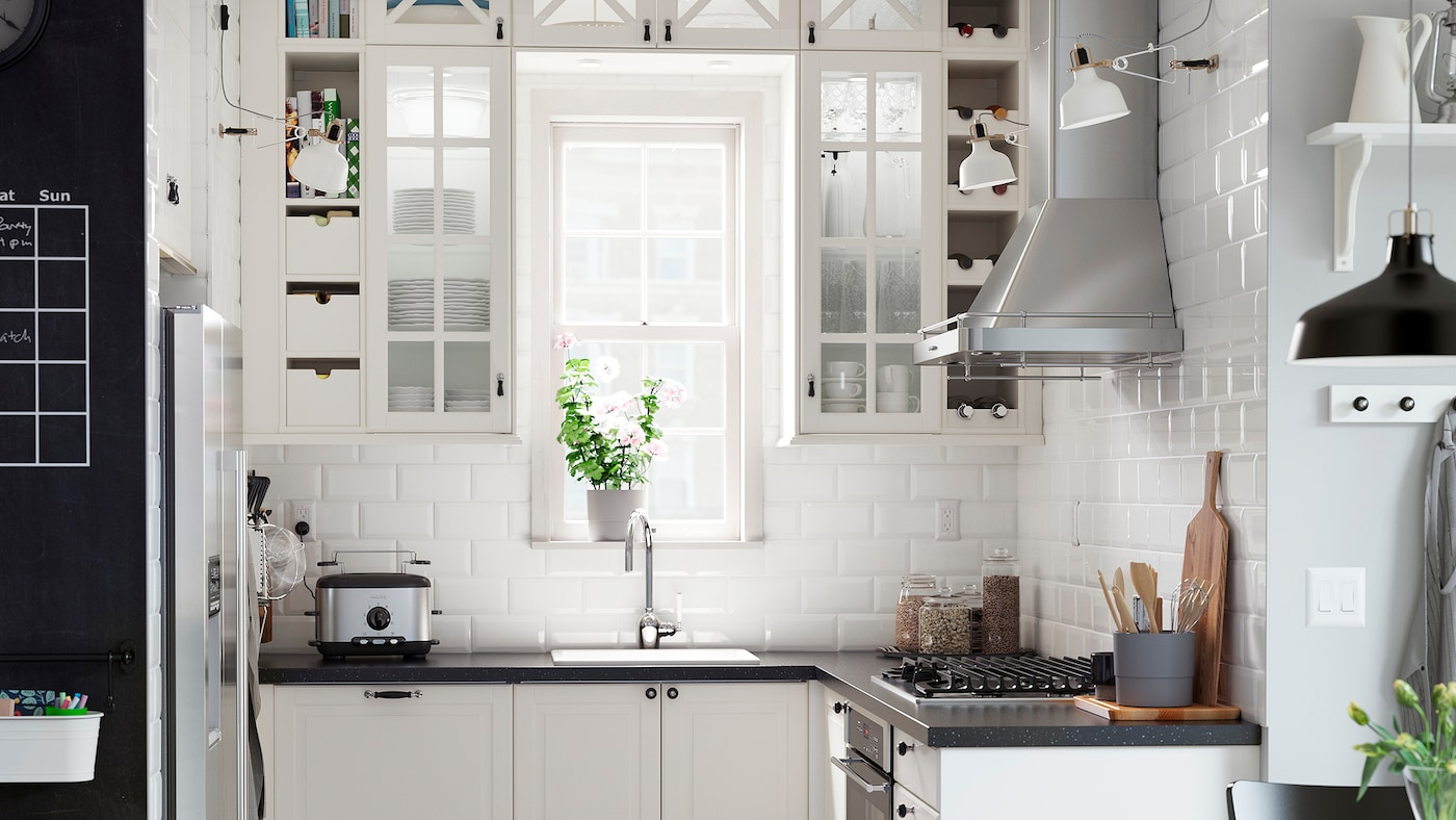A kitchen with off-white glass-doored cabinets arranged around a window and a black mineral effect worktop.