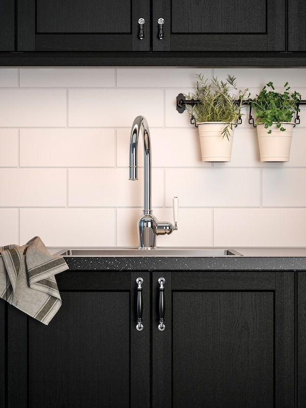 A kitchen with stained black cabinet fronts, a black mineral-effect worktop and a chrome-plated mixer tap.
