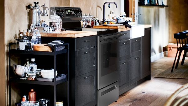 A kitchen with stained black LERHYTTAN cabinet fronts, an oak/veneer worktop and a white sink with visible front.