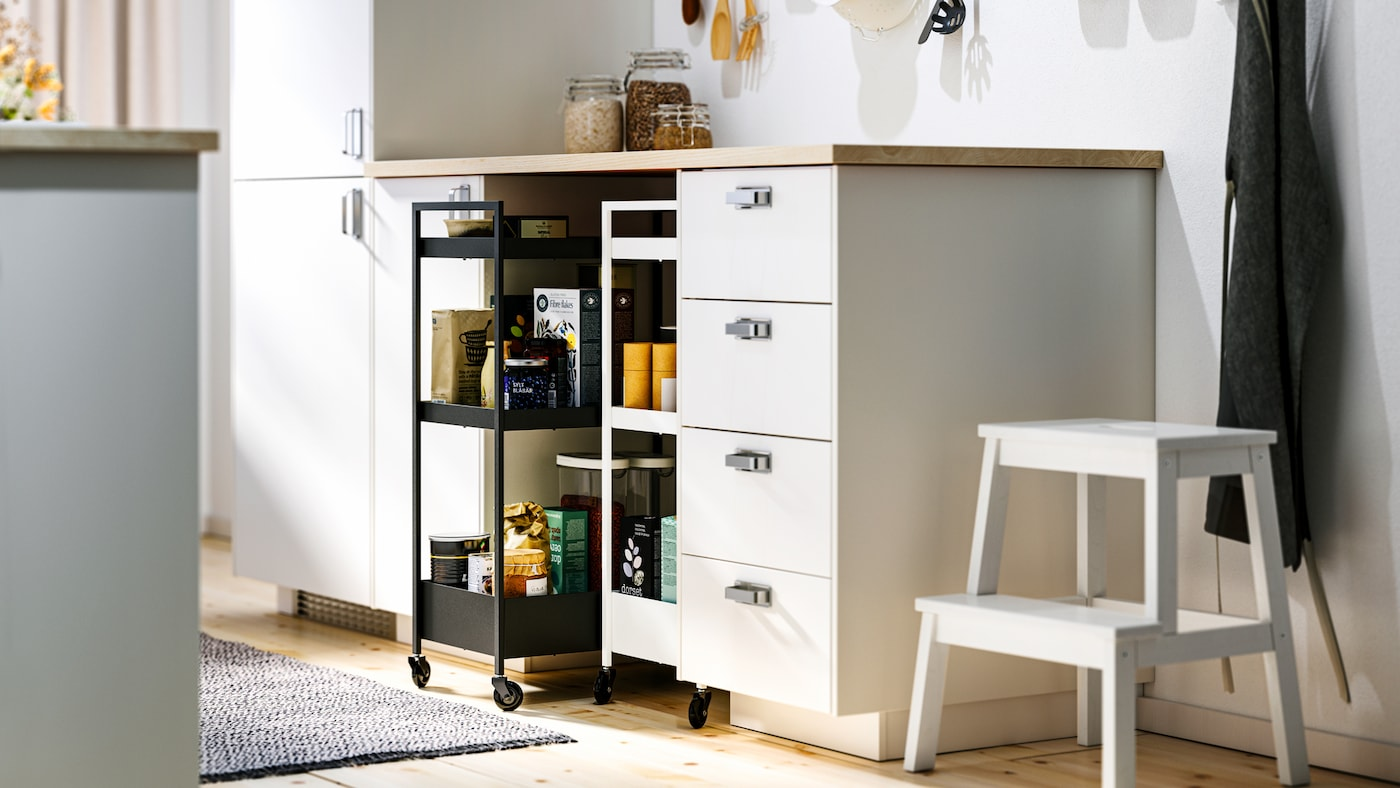 A kitchen with white METOD base cabinets and MAXIMERA interiors, an EKBACKEN benchtop and two NISSAFORS trolleys.