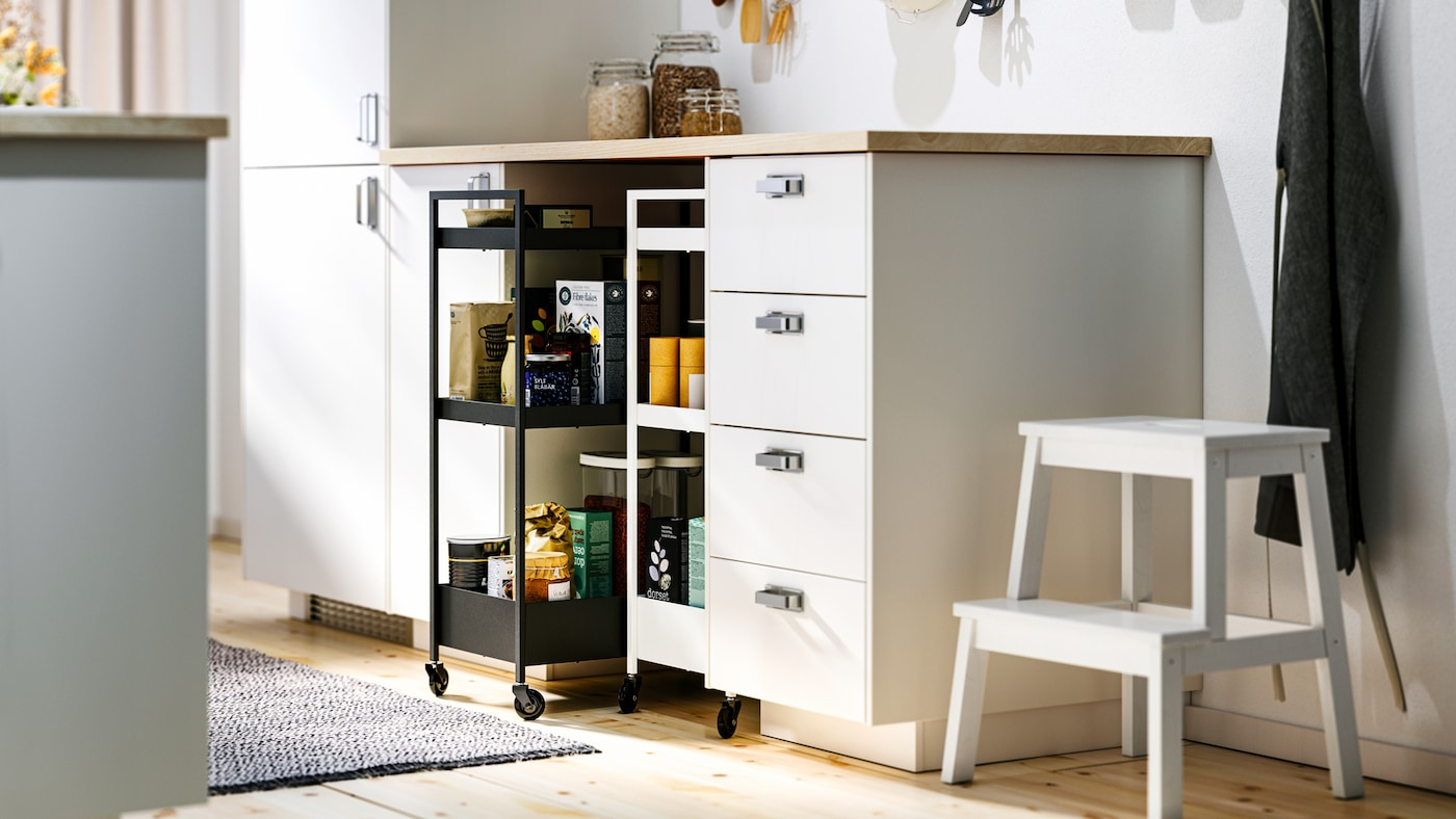 A kitchen with white METOD base cabinets and MAXIMERA interiors, an EKBACKEN worktop and two NISSAFORS trolleys.