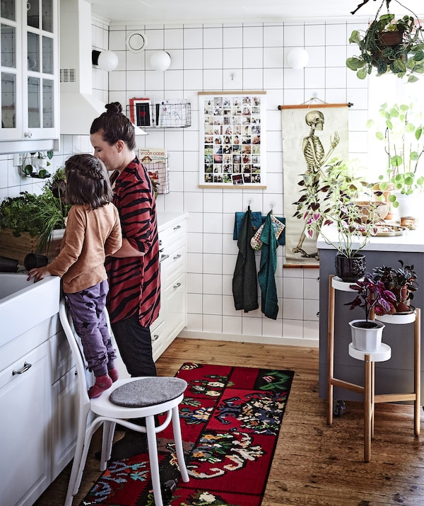 A kitchen with white units, hanging tea towels and a plant stand.