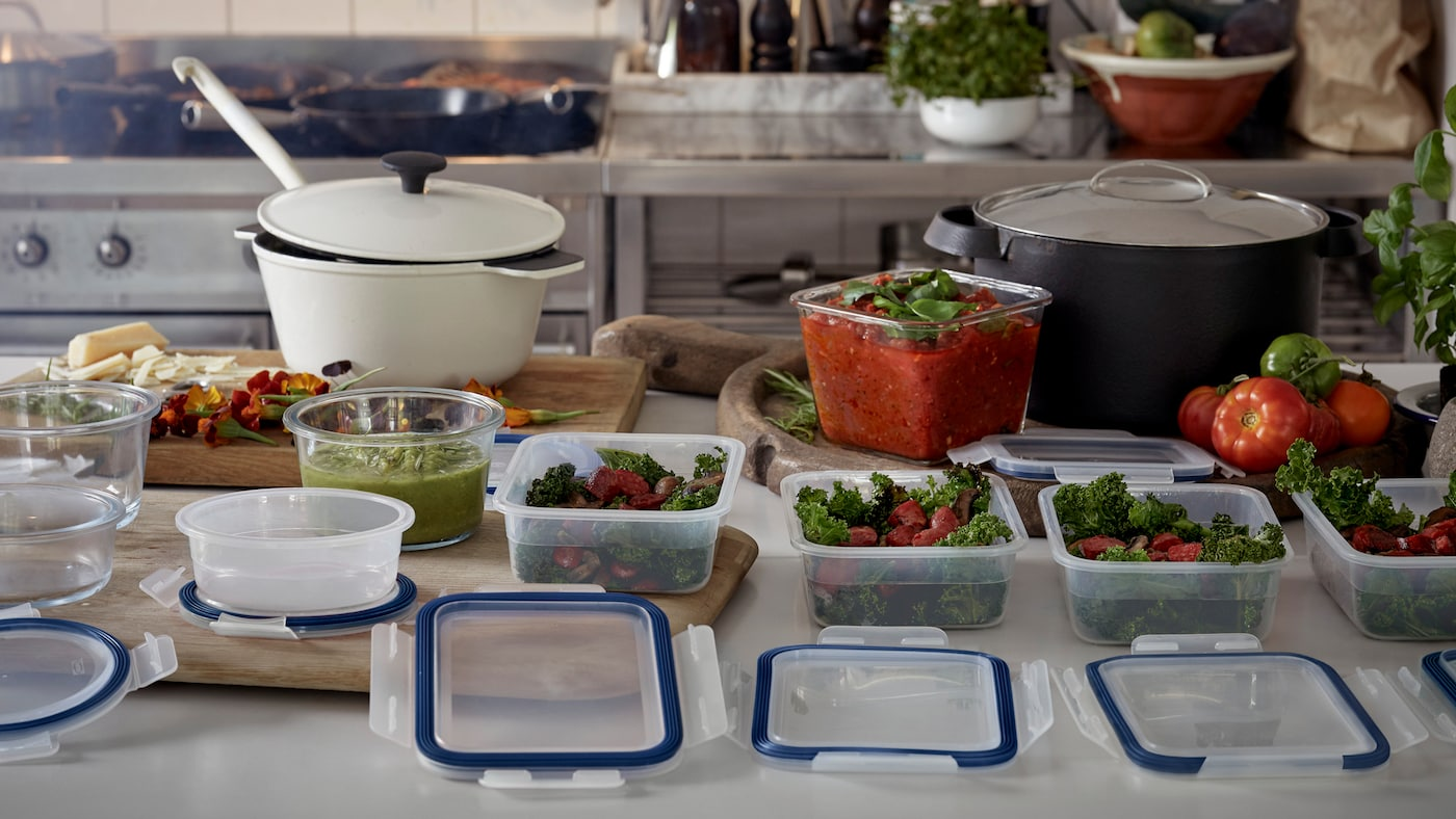 A kitchen workbench where food prep is underway with several food containers in various stages of being filled.