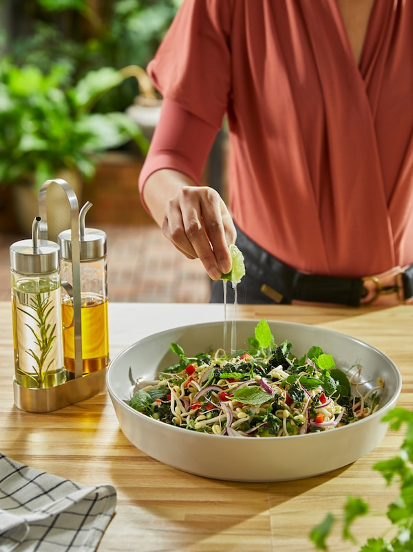 A kitchen worktop and a salad plate with an ÖRTFYLLD three-piece oil and vinegar set in glass and stainless steel beside it.