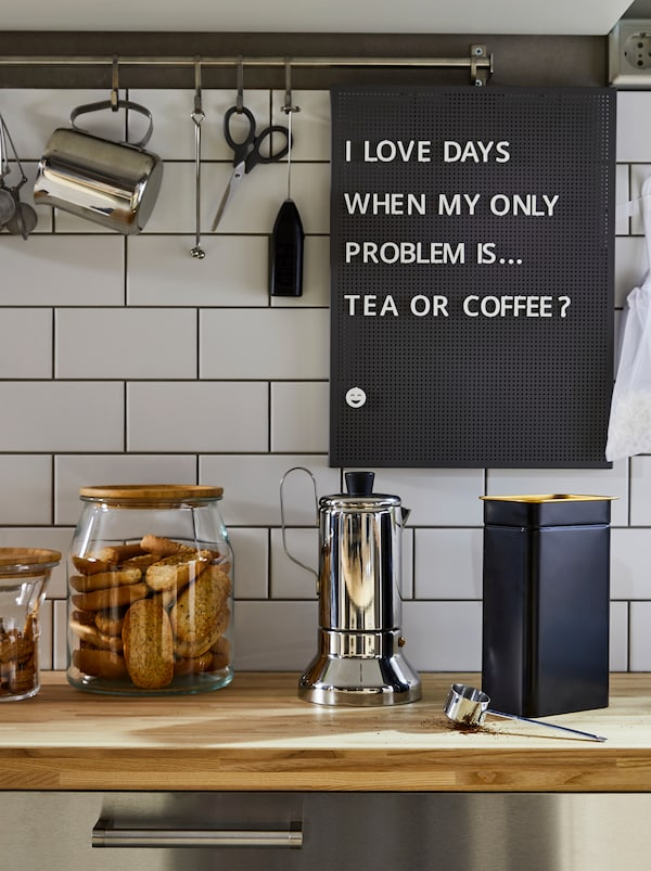 A kitchen worktop with a METALLISK espresso maker in stainless steel, a blue BLOMNING coffee tin and glass jars for cookies.