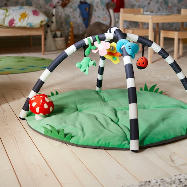 A KLAPPA baby gym placed on a light wooden floor. Behind it are a children's bed, children's table and chairs, and toys.