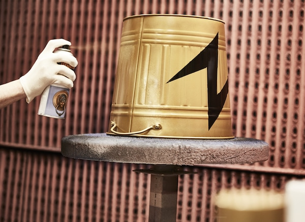 A KNODD bin is flipped upside down and spray painted gold with a black lightening bolt.