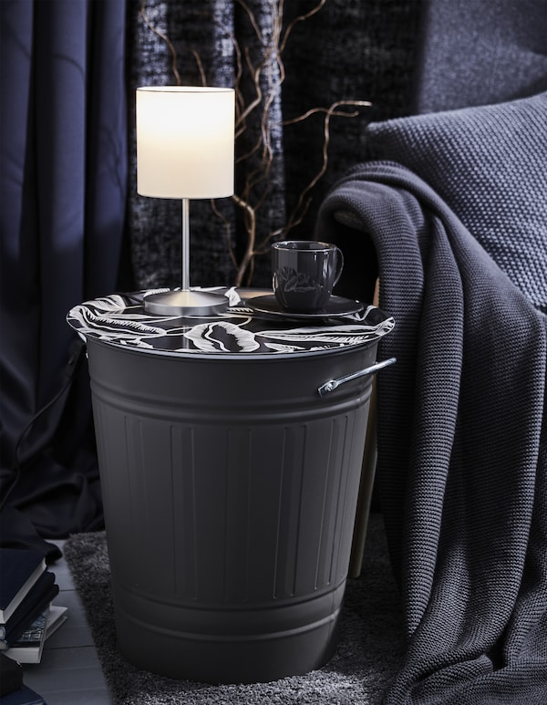 A KNODD bin is topped with a decorative tray to create a side table, and has a lamp and cup of coffee resting on it.