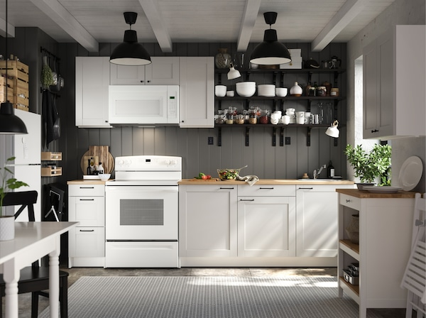 A KNOXHULT kitchen in light grey, black wall-mounted shelves, a white kitchen table, a black chair and a black pendant lamp.
