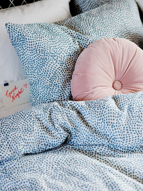 A KRANSBORRE cushion in light pink is tucked underneath a TRÄDKRASSULA duvet cover in white and blue.