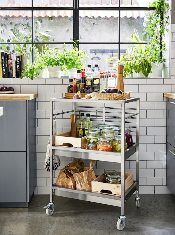 A KUNGSFORS kitchen trolley in stainless steel with three shelves and wheels, filled with spices and pickle jars.
