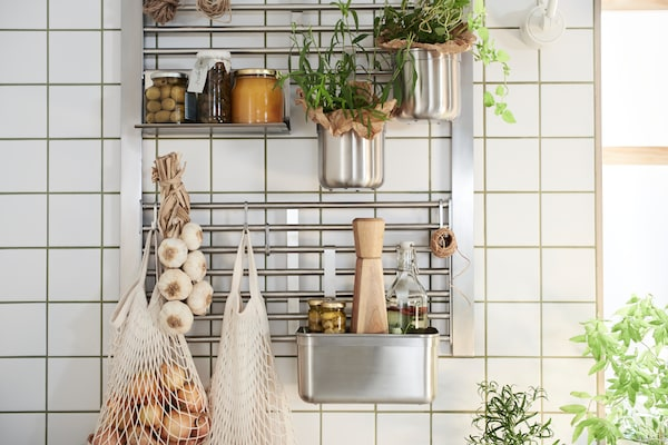 A KUNGSFORS stainless steel wall grid with jars, herbs, a string of garlic and a container of condiments attached to it.