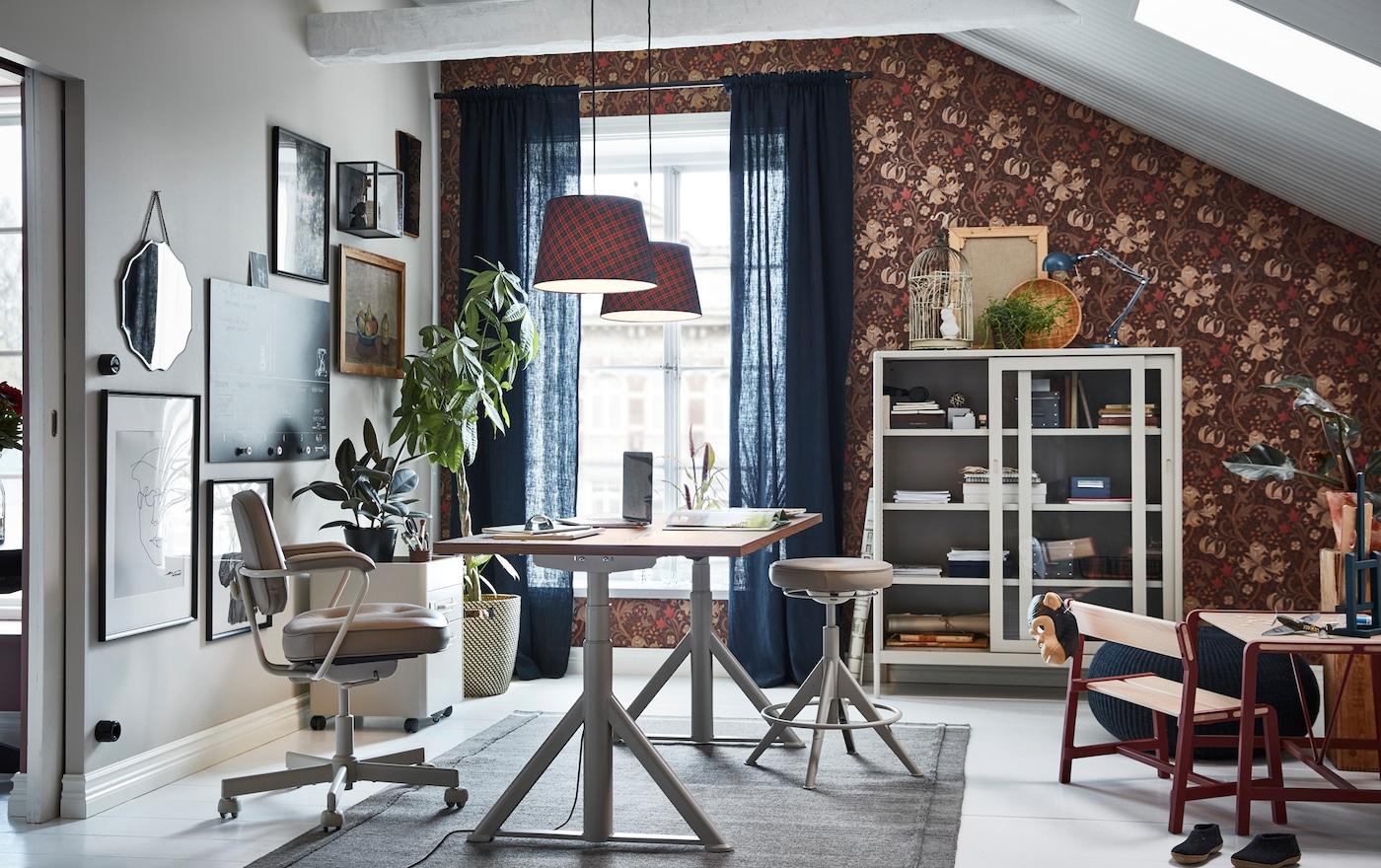 À la fois fonctionnels et modernes, le bureau assis/debout, le caisson à tiroirs et la vitrine beiges IKEA IDÅSEN apportent un équilibre au bureau à domicile.