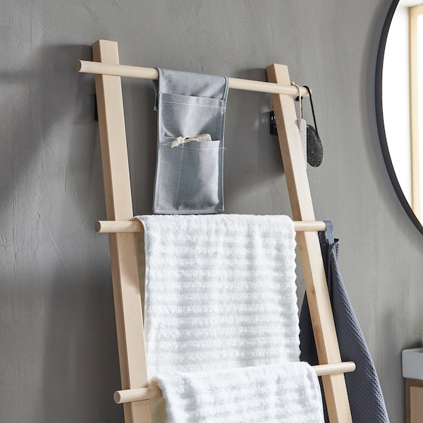 A ladder-like VILTO towel stand in birch wood leaning against the grey wall of a minimalistic bathroom.
