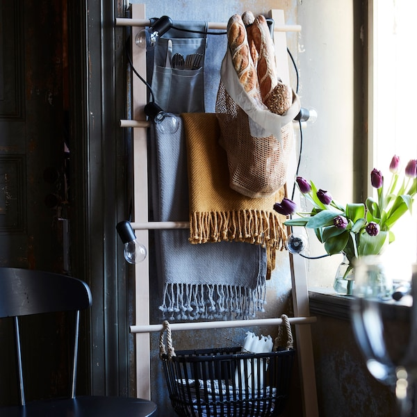 A ladder with scarves, cutlery, and baguettes in a mesh bag.