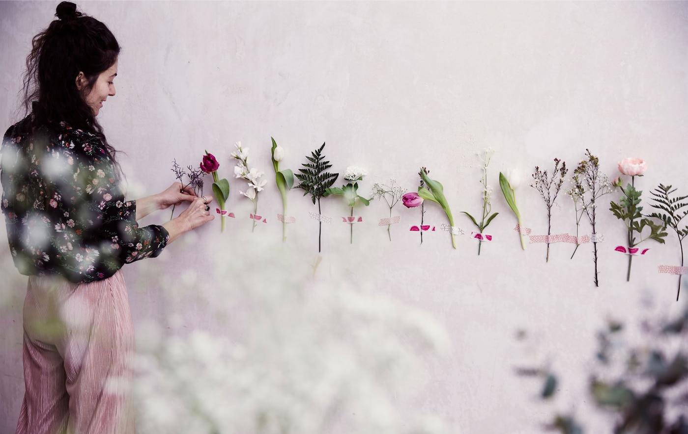 À l'aide de ruban adhésif, Julia colle des fleurs sur un mur blanc.