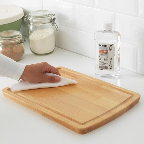À l'aide d'un chiffon, une main applique une huile pour bois SKYDD sur une planche à découper, devant une bouteille contenant le produit.