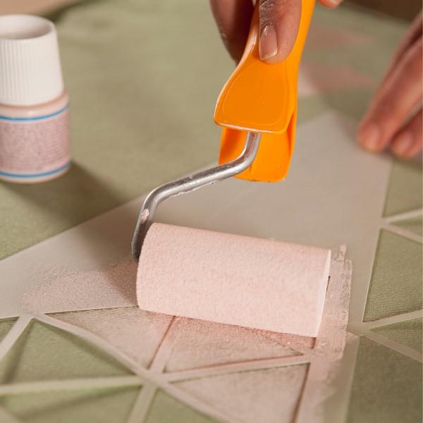 à l'aide d'un pochoir et d'un rouleau à peindre, tracer au pochoir un triangle rose sur le tissu