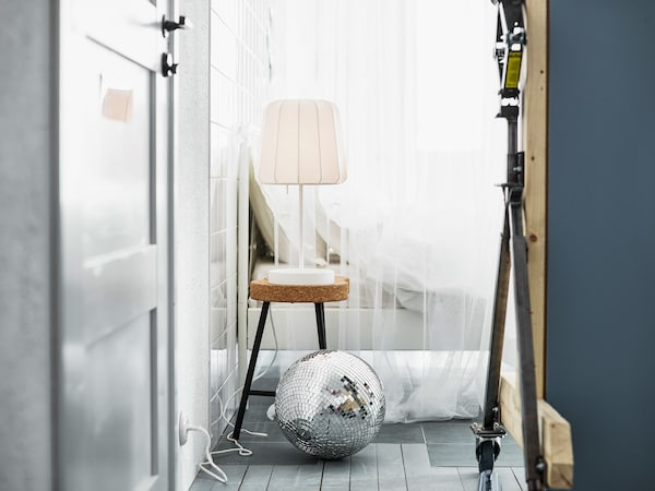 A lamp on a cork stool next to a bed dressed in white textiles and a loose disco ball.