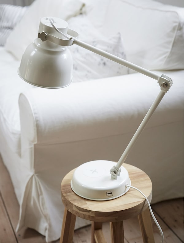 A lamp on a wooden stool next to a white sofa.