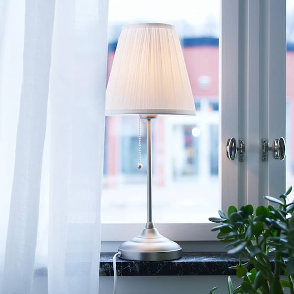 A lamp with a white pleated shade and thin metal stem sits on a window sill beside a green plant.