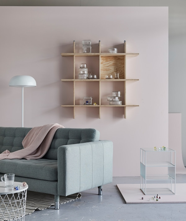 A LANDSKRONA sofa and sparsely filled wall shelves in a pale living room.