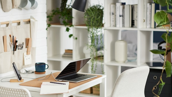 A laptop on a white table with one white and one beige chair, beside a white shelving unit with books, plants and storage.