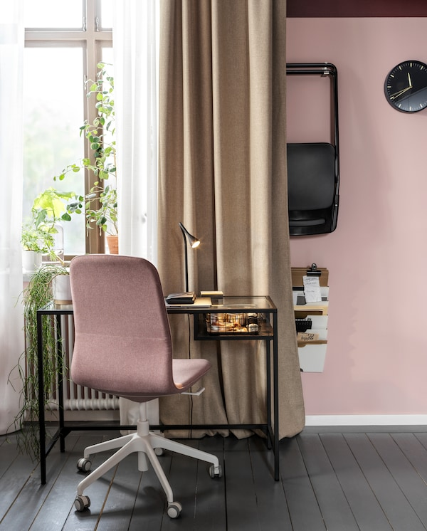 A laptop table in black-brown/glass and a light brown-pink conference chair stand by a window with beige and white curtains.