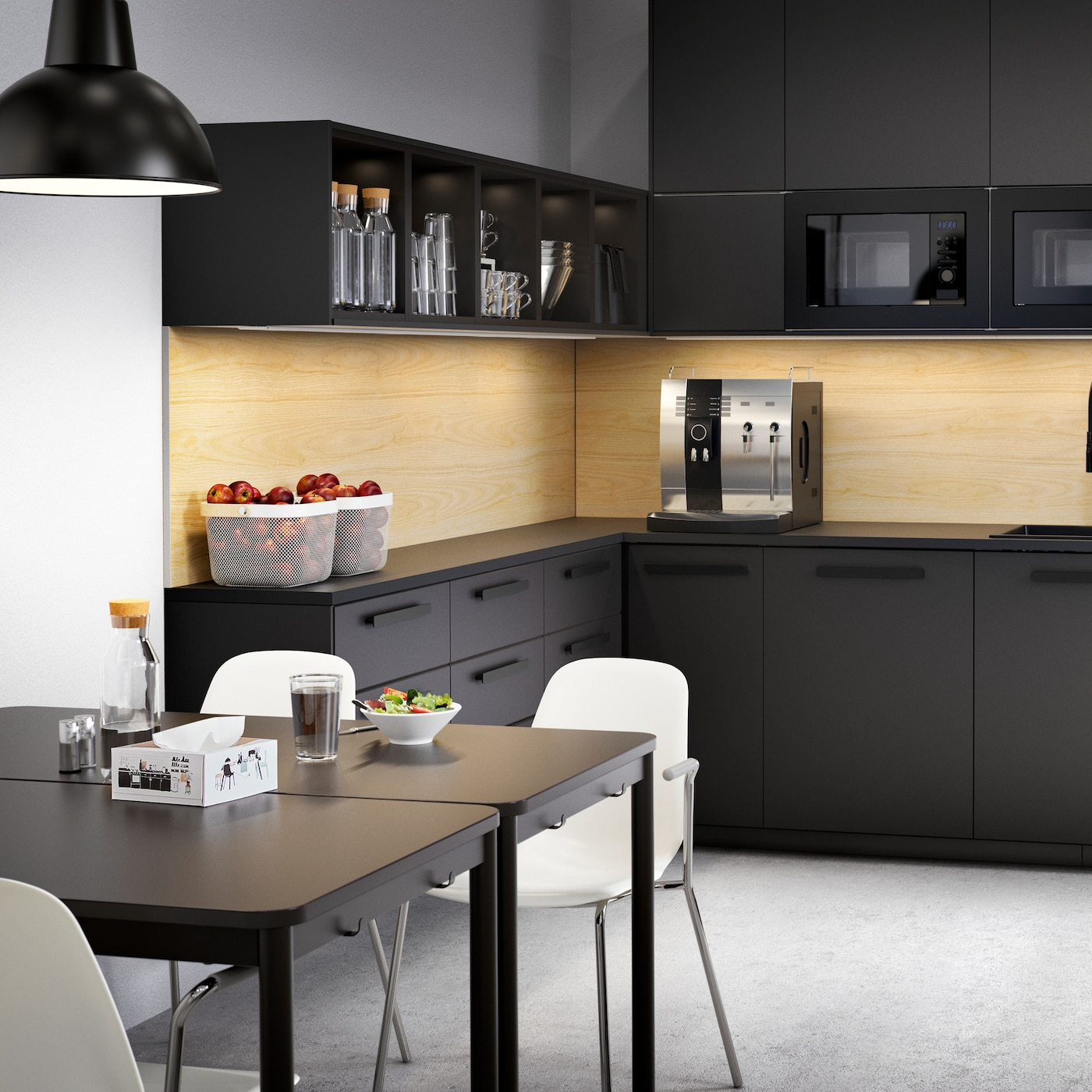 A large anthracite kitchen with drawers and cabinets, coffee machine, bowls with fruits and two tables with white chairs.