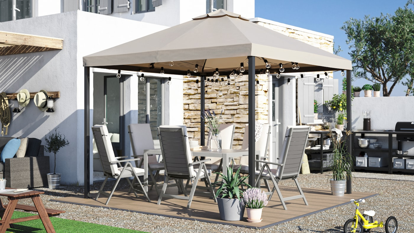 A large backyard with a dining table, outdoor chairs with cushions, a gazebo, wood-like decking and an outdoor kitchen.