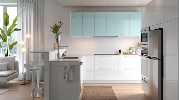 A large, bright open-plan kitchen with white and turquoise door fronts, and a link leading to a gallery of kitchen ideas.